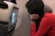 Teenage girl looking at the options on the inflight entertainment screen traveller letters inflight entertainment