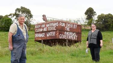 John McKenzie and sister Heather Dodd in front of protest signs against the dumping of toxic soil from the Metro Tunnel opposite their property in Bulla.