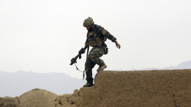 A US special operations forces soldier climbs down from a compound wall in Shewan, a former Taliban stronghold in Afghanistan's Farah province.