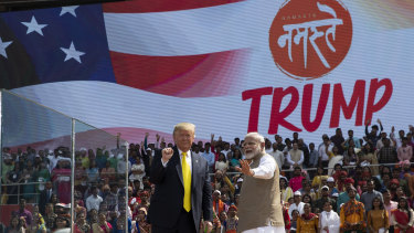 "Donald Trump and Narendra Modi wave after a ""Namaste Trump"" event at Sardar Patel Gujarat Stadium."