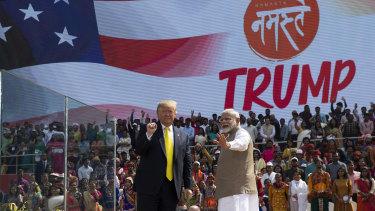 "US President Donald Trump and Indian Prime Minister Narendra Modi wave after a ""Namaste Trump"" event at Sardar Patel Gujarat Stadium."