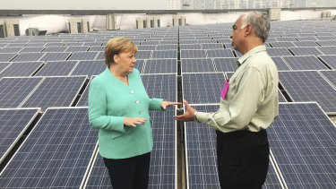 German Chancellor Angela Merkel speaks with an officer as she looks at solar panels on the roof of a metro station in New Delhi, India.