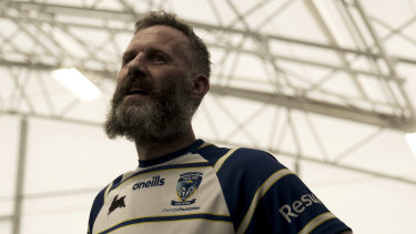 Adam Hills wearing his Warrington Wolves jersey in the documentary Take His Legs.