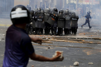 A demostrator prepares to hurl a rock at police during a protest in Honduras.