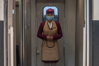 A train attendant stands on a train to Wuhan, the epicentre of the global outbreak, at a railway station in Beijing on Sunday.