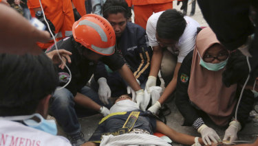 Rescuers check a survivor at restaurant building damaged by a massive earthquakes and tsunami in Palu.