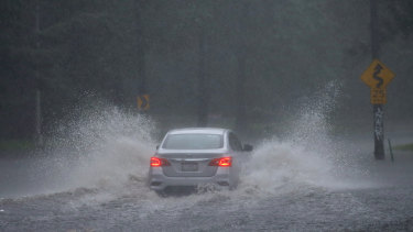 A car drives down a flooded street during Tropical Storm Isaias in Philadelphia.