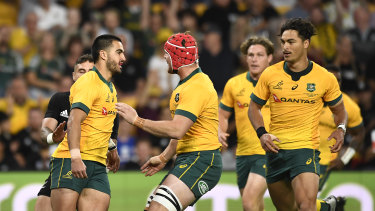 Wallabies teammates congratulate Tom Wright after his early try on debut.