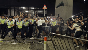 Police officers use pepper spray against protesters.