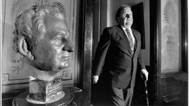 Ald. Doug Sutherland passes a bust of himself as he leaves his office.
