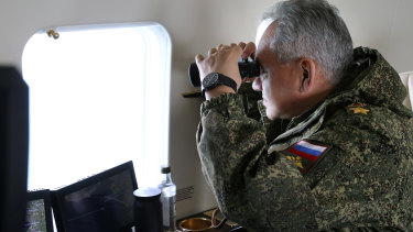 Russian Defense Minister Sergei Shoigu watches drills form a board of military helicopter in Crimea.