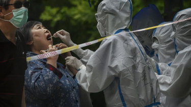 A Chinese epidemic control worker wears a protective suit and mask while performing a nucleic acid test for COVID-19 on a woman at a testing center in Beijing.