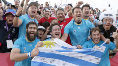 Triumphant Uruguayan players celebrate with the crowd after their stunning defeat of Fiji in the World Cup.