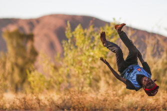 A boy performs a flip ahead of community celebrations at Uluru.