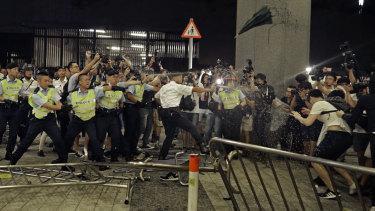 Les policiers utilisent un spray au poivre contre les manifestants.