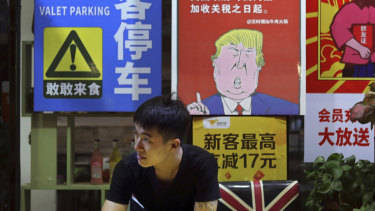 A man in Guangzhou stands near a poster depicting a mural of Donald Trump stating that all American costumers will be charged 25 per cent more than others starting from the day he started the trade war against China.