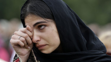 A woman wipes away tears during a gathering for the 'March for Love' in Hagley Park, Christchurch.
