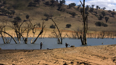A couple of fishermen on the enlarging banks of Lake Hume, near Albury, where water levels are low due to drought.