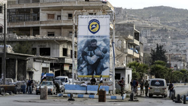 Syrian opposition fighters control a car at a checkpoint in north-western city of Idlib, Syria, late on Saturday.