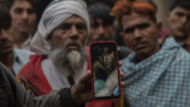A man holds a phone in January this year showing a video of Muslim farmer moments after being beaten for allegedly smuggling cows in Mirzapur, India.