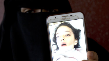 Aisha's mum Muna Awad shows a photo of her sent to her parents while she was in a Jerusalem hospital.