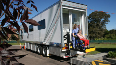 A clinic manager for Australian Aged Dental Care loads an elderly lady into a van outside a retirement home in Wyee in 2012.