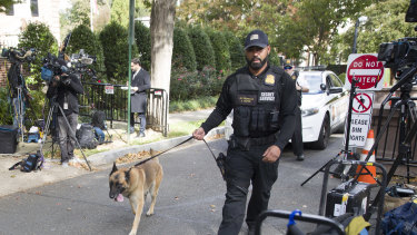 An officer with the Uniform Division of the United States Secret Service uses his dog to search a checkpoint near the home of President Barack Obama.