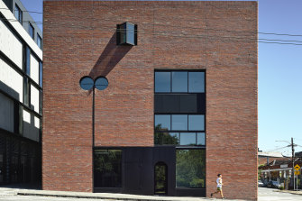 The solid brick and masonry development includes four levels but reads from the street as two generous levels.