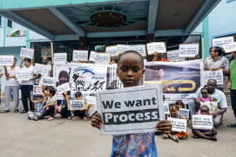 Families demonstrate outside Hotel Kolekta, a rundown establishment that has become their home for years on end. This accommodation is arranged by the International Organisation for Migration, which relies on Australian government funding.