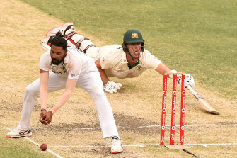 Mohammed Siraj of India fields as Pat Cummins of Australia makes his ground.