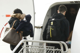 Richmond's Trent Cotchin and his family board a flight to Queensland earlier this month.