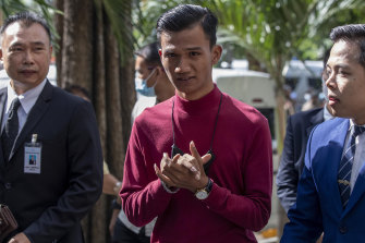 Pro-democracy activist Panupong Jadnok (centre) arrives at a Bangkok court for a hearing to determine whether he had violated his bail conditions.