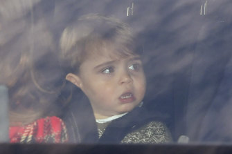 Prince Louis sits in the back of a car driven by his mother.