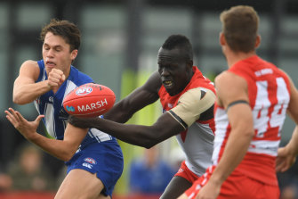 North Melbourne's Curtis Taylor gets a handball away despite the attention of Sydney's Aliir Aliir in Hobart during the pre-season.