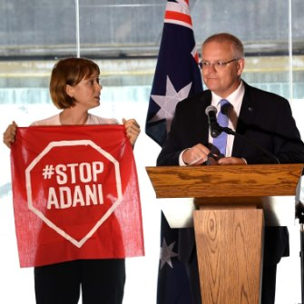 A Stop Adani protestor takes to the stage with Prime Minister Scott Morrison during the campaign.