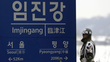 A South Korean soldier stands near a signboard showing the distance to Pyongyang and to Seoul from Imjingang Station in Paju, South Korea.