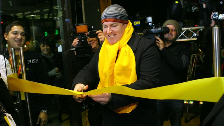 The first man to receive an iPhone 3G cuts the ribbon to the store.
