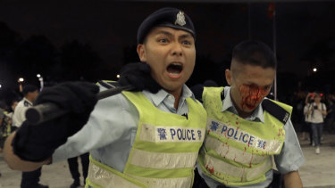A Hong Kong police officer being assisted by his colleague after clashing with protesters.