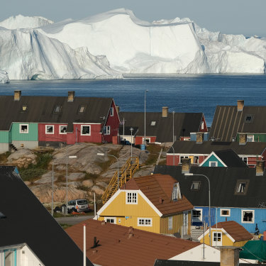 The town of Ilulissat with icebergs looming at the mouth of its fjord in July.