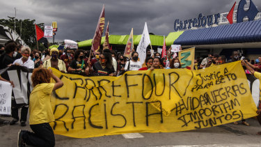 Demonstrators hold banners and signs in front of the entrance to the Carrefour Niteroi-Manilha branch as protests erupt against racism in Brazil.