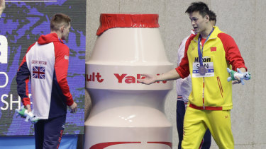 Gold medlaist China's Sun Yang, right, gestures to Britain's bronze medalist Duncan Scott.