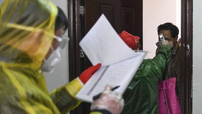 Authorities search door-to-door for coronavirus in Wuhan as cases fall
