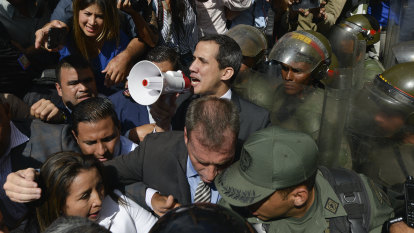 Venezuela's Guaido forces his way into parliament, takes oath in darkness