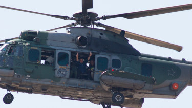 President Jair Bolsonaro waves at supporters from a helicopter in Brasilia, Brazil.