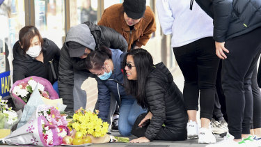 Thomas Tran's family in Eaton Mall where he died on Monday night. Mr Tran's mother Amy (right) sobs on the ground.