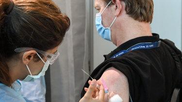 A Qantas pilot receives his vaccination from registered nurse Hedi Soleiman.