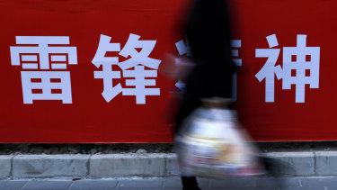 "A woman carries her groceries past a Chinese propaganda board depicting ""Lei Feng Spirit"" on a pavement in Beijing on Tuesday."