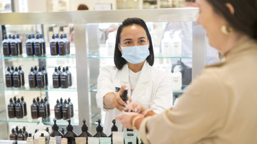 Testing times ... Okta Sampurna (left) helps a customer at the Grown Alchemist counter at David Jones in Melbourne, which has implemented several hygiene changes in its beauty department.