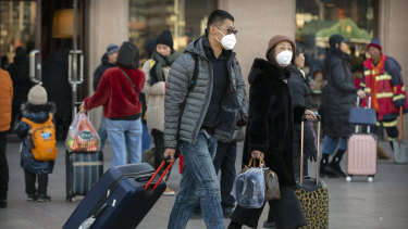 Travellers wear face masks in Beijing as  China reported a sharp rise in the number of people infected with coronavirus.
