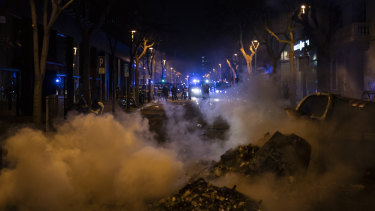 Police officers stand guard near a burning barricade setup by demonstrators at the end of a protest condemning the arrest of rap singer Pablo Hasél in Barcelona, Spain.